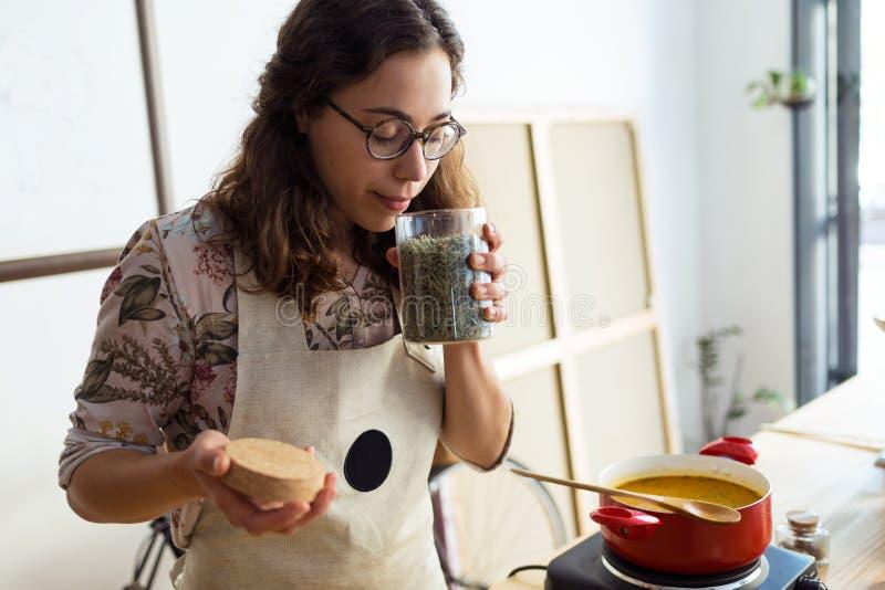 Bella donna che cucina e che odora gli aromi piacevoli dalle spezie in un vaso in deposito organico fotografia stock libera da diritti