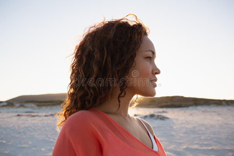 Bella donna che distoglie lo sguardo sulla spiaggia immagine stock