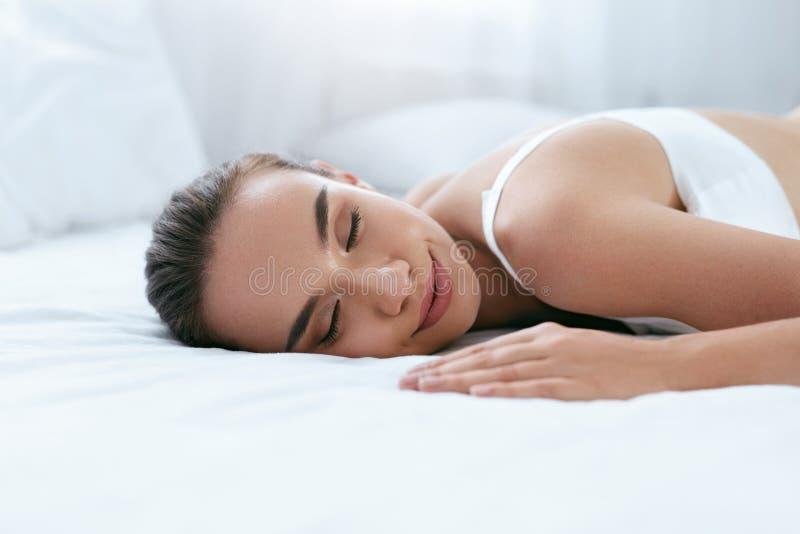 Bella donna che dorme sul letto bianco nell'interno leggero immagini stock libere da diritti