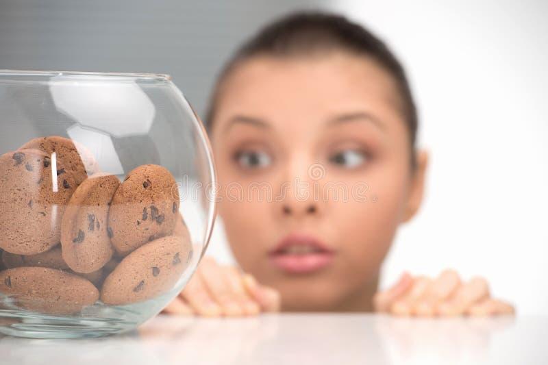 Bella donna che esamina i biscotti sulla tavola fotografie stock