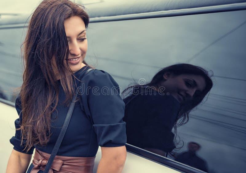 Bella donna che esamina l'uomo nella riflessione di vetro automobilistico immagine stock libera da diritti