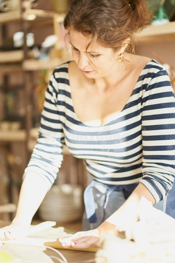 Bella donna che fa gli articoli ceramici in posto di lavoro, luce del sole Concetto per la donna in indipendente, affare, hobby immagini stock libere da diritti