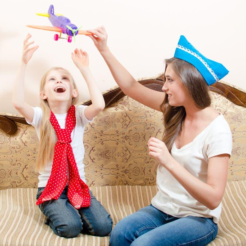 Bella donna che gioca aeroplano con la ragazza del bambino, divertendosi, seduta sorridente felice sul sofà fotografia stock libera da diritti