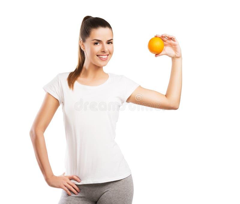 Bella donna che giudica un'arancia isolata su bianco fotografia stock