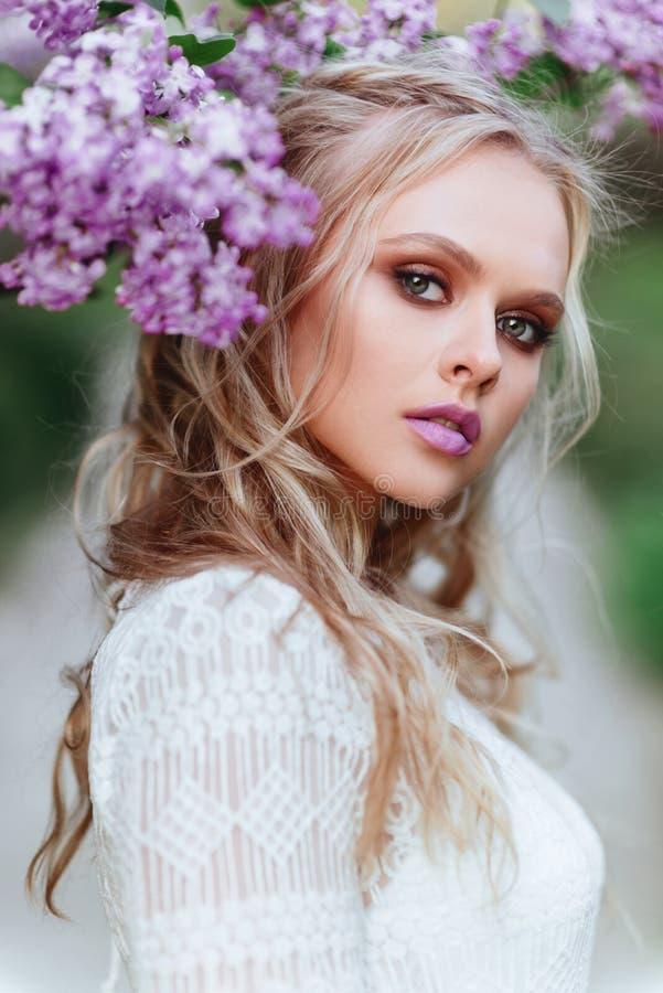 Bella donna che gode del giardino lilla, giovane donna con i fiori in parco verde fotografia stock