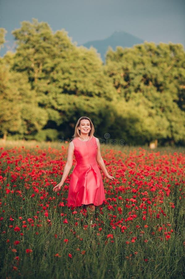 Bella donna che gode del giorno piacevole nel campo del papavero immagini stock