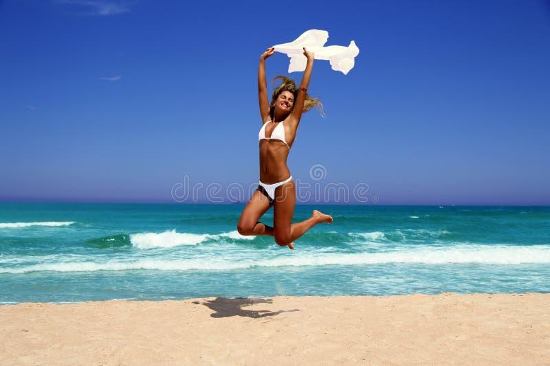 Bella donna che gode del sole davanti all'oceano. immagine stock