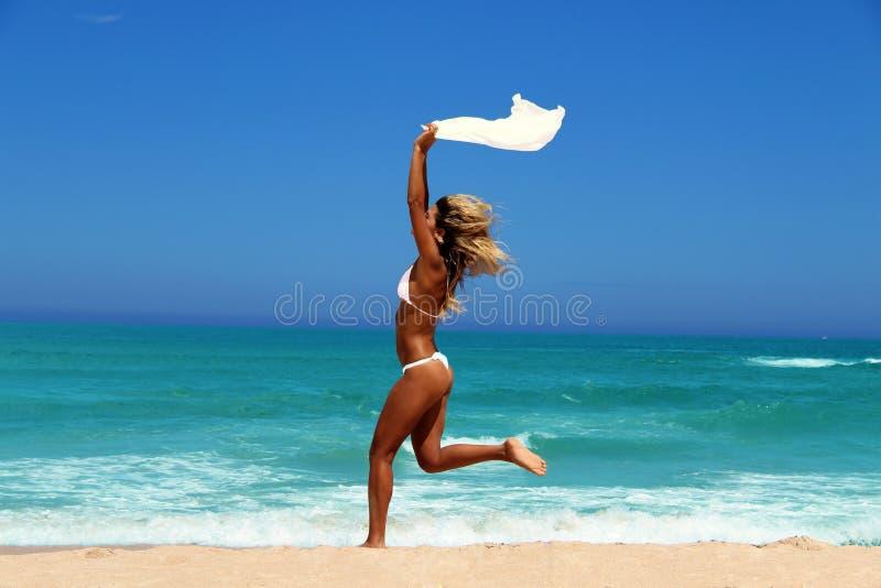 Bella donna che gode del sole davanti all'oceano. fotografia stock