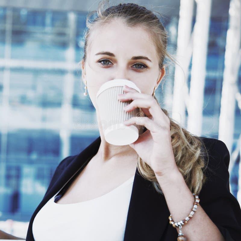 Bella donna che gode in una bevanda della tazza di caffè, atto di affari immagine stock