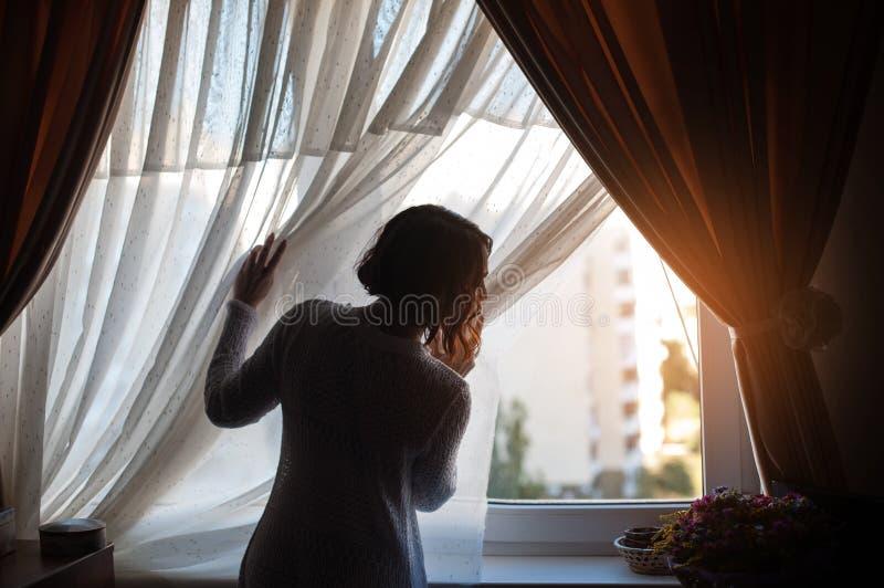 Bella donna che guarda attraverso la finestra nella stanza scura immagine stock