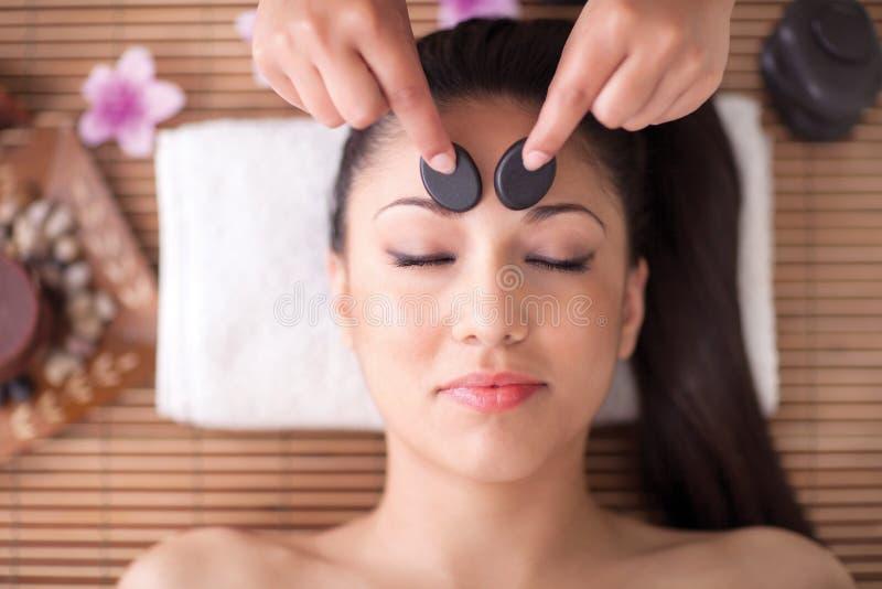 Bella donna che ha un massaggio della testa di benessere con le pietre fotografia stock