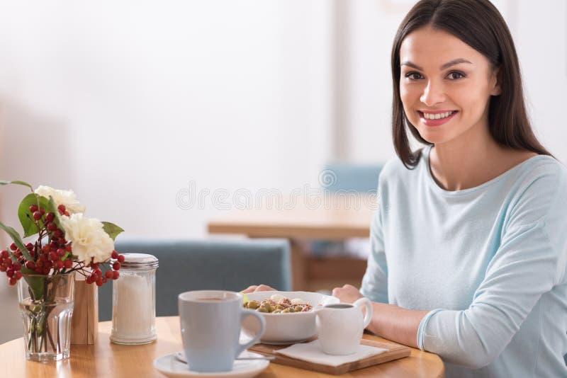 Bella donna che ha un pasto in caffè fotografia stock libera da diritti