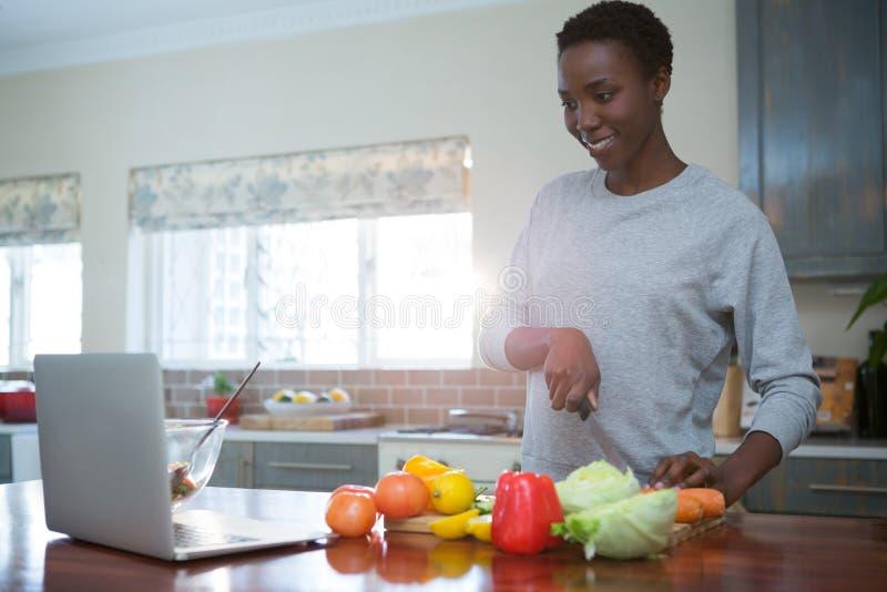 Bella donna che impara ricetta dell'alimento dal computer portatile fotografie stock libere da diritti