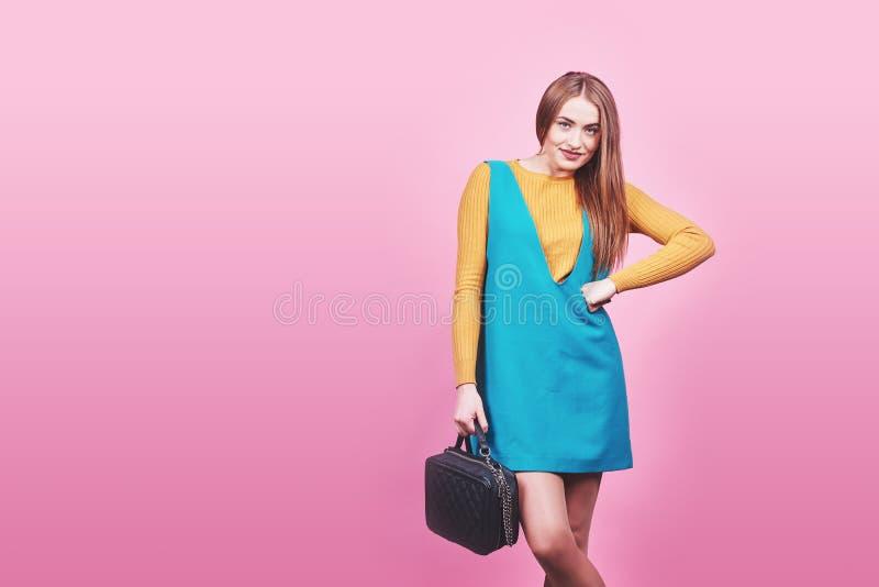 Bella donna che indossa i vestiti piacevoli, borsa che posa sul fondo rosa Foto della molla di modo immagini stock