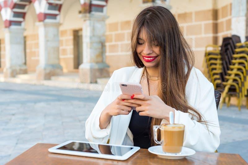 Bella donna che mangia un caffè con un cellulare e una compressa immagini stock libere da diritti