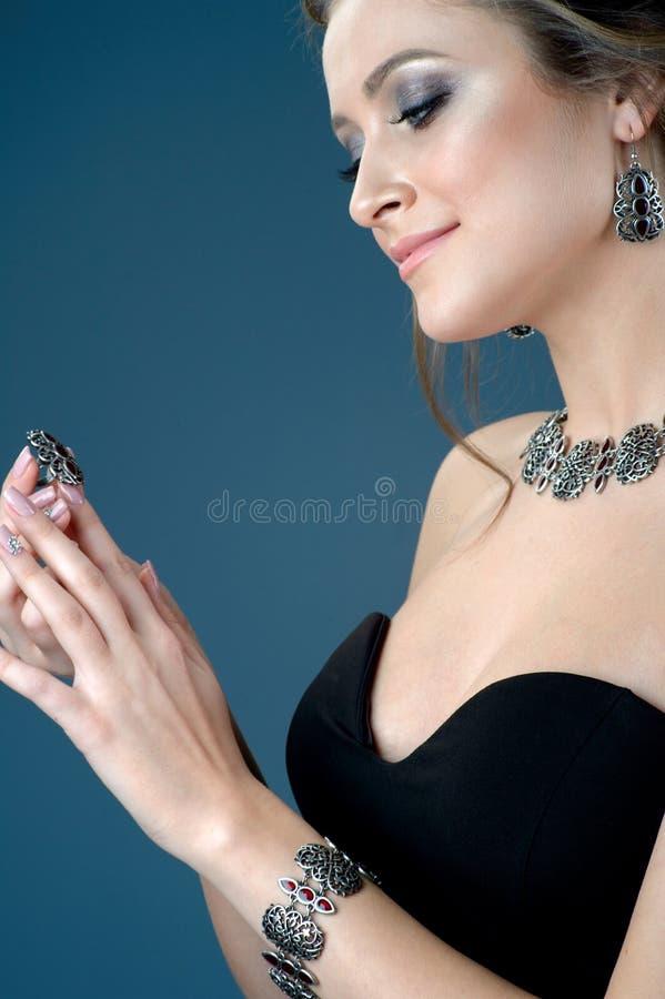 Bella donna che mostra gli orecchini collana ed anello su buio blu fotografia stock
