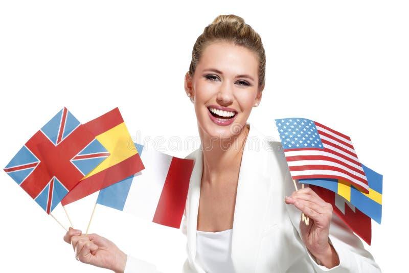 Bella donna che mostra le bandiere internazionali fotografia stock libera da diritti