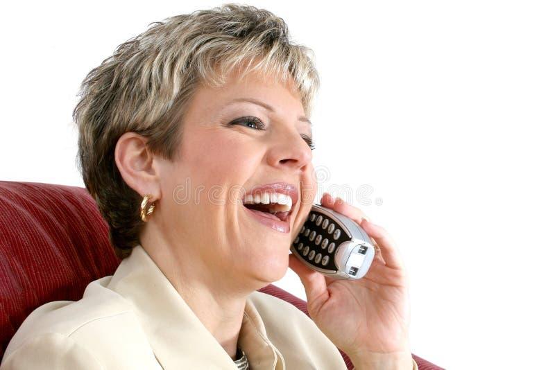 Bella donna che parla su un telefono senza cordone della Camera sopra bianco fotografie stock libere da diritti