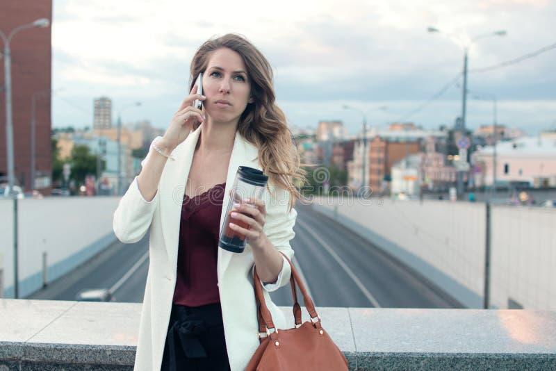 Bella donna che parla sul telefono che cammina sulla via Ritratto della donna sorridente alla moda di affari in vestiti alla moda fotografie stock libere da diritti