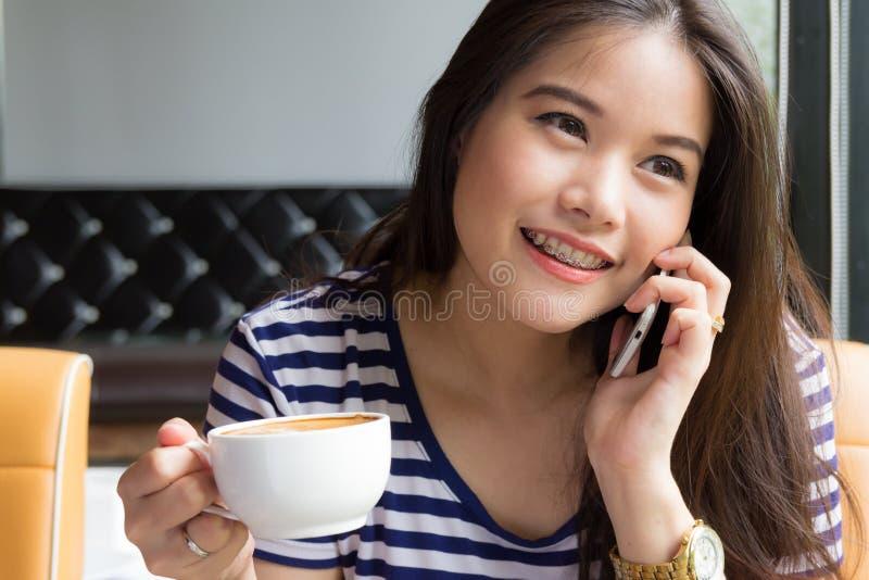 Bella donna che parla sul telefono e che tiene tazza di caffè immagine stock