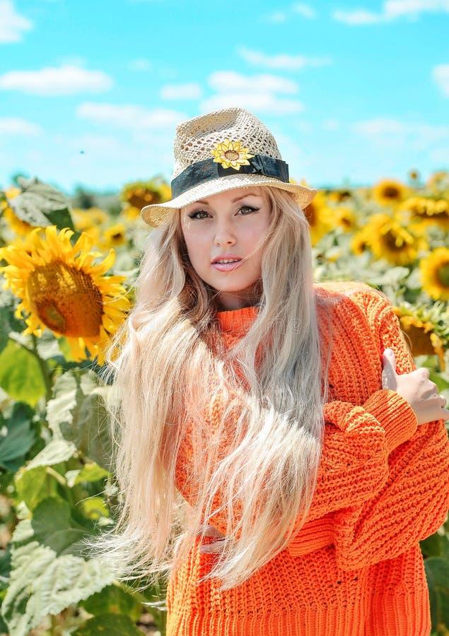 Bella donna che posa in maglione arancio sul prato con i girasoli immagine stock