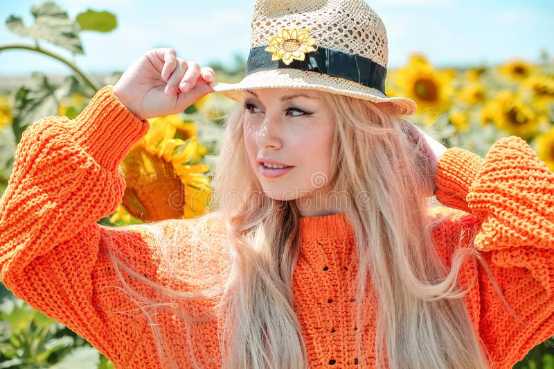 Bella donna che posa in maglione arancio sul prato con i girasoli fotografia stock