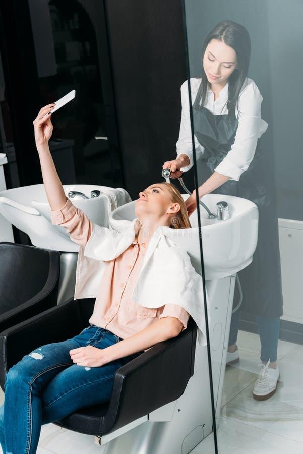 bella donna che prende selfie mentre parrucchiere che lava i suoi capelli fotografia stock libera da diritti