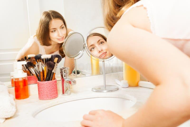 Bella donna che pulisce il suo fronte con il cuscinetto di cotone fotografia stock