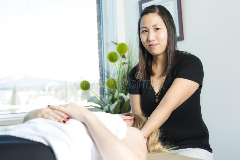 Bella donna che riceve massaggio dal terapista fisico immagine stock