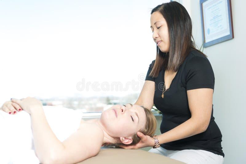 Bella donna che riceve massaggio dal terapista fisico fotografia stock libera da diritti