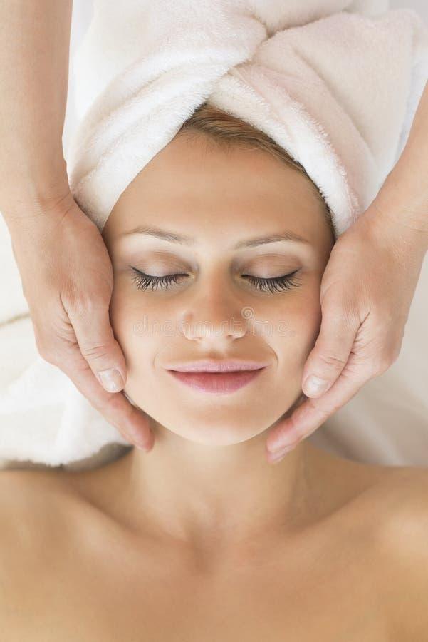 Bella donna che riceve massaggio facciale in stazione termale immagini stock libere da diritti