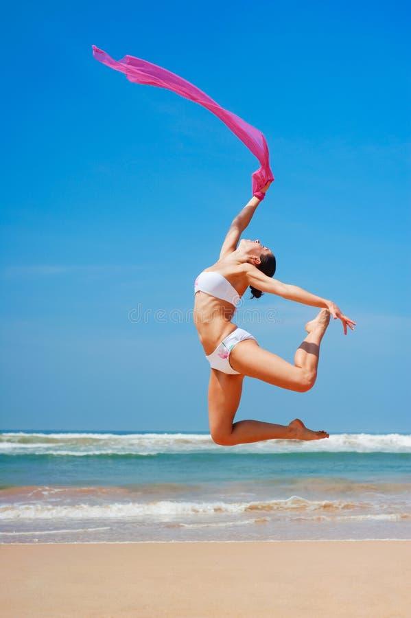 Bella donna che salta alla spiaggia fotografia stock libera da diritti