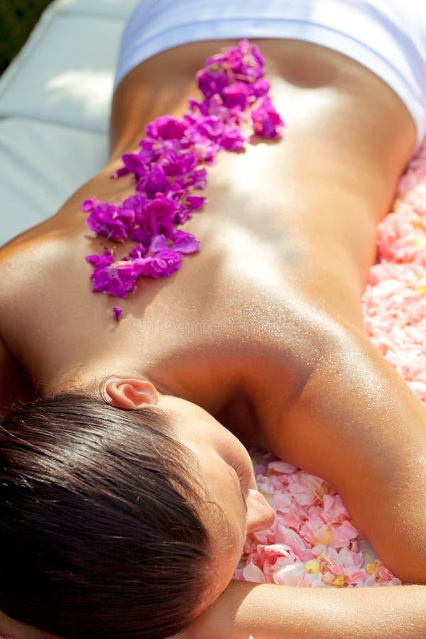 Bella donna che si distende sulla tabella di massaggio fotografia stock