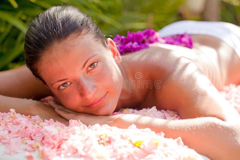 Bella donna che si distende sulla tabella di massaggio fotografia stock libera da diritti