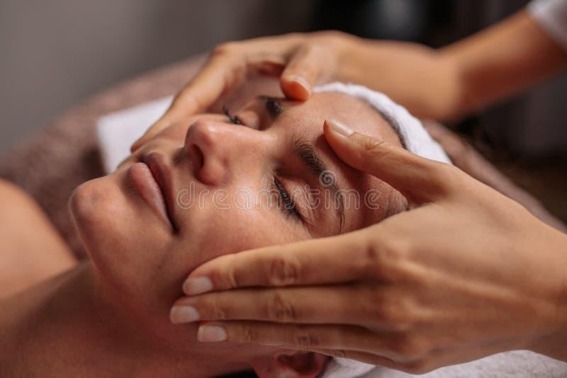 Bella donna che si rilassa con il massaggio di fronte alla stazione termale di bellezza immagini stock