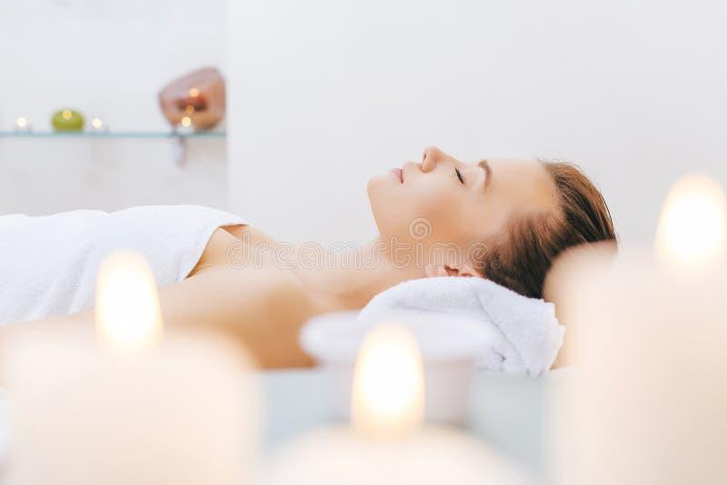 Bella donna che si rilassa sulla Tabella di massaggio immagine stock