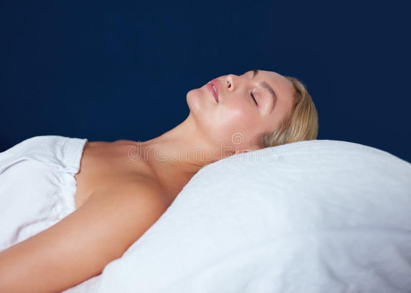 Bella donna che si rilassa sulla Tabella di massaggio alla stazione termale fotografie stock