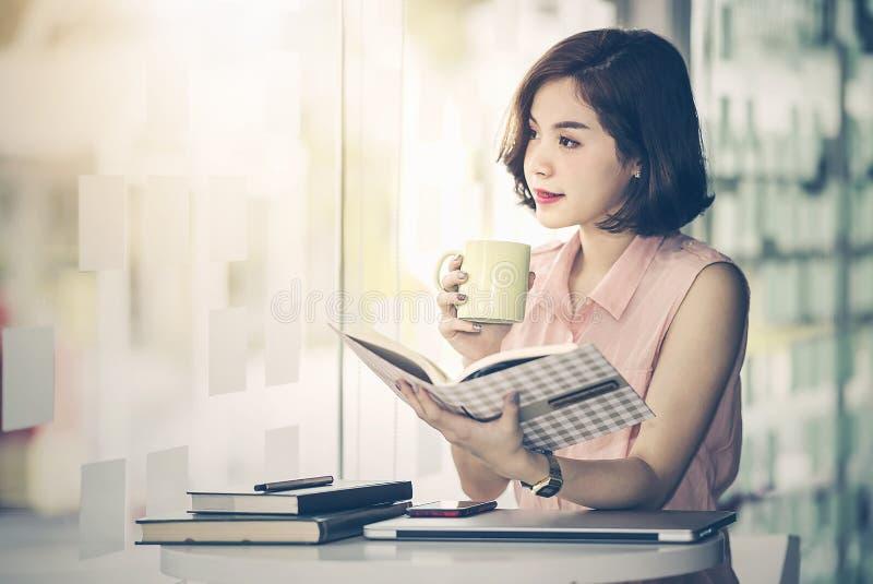 Bella donna che si siede al suo scrittorio che tiene tazza di caffè immagine stock