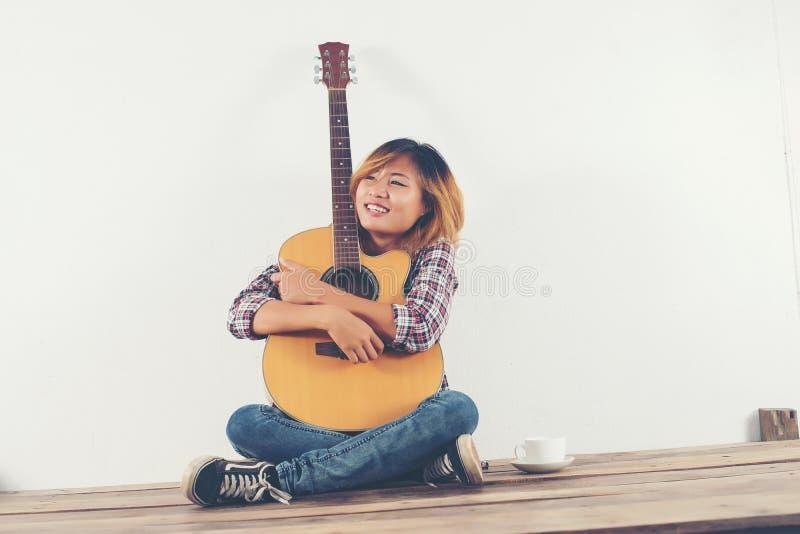 Bella donna che si siede con la sua seduta felice della chitarra sul corteggiare immagine stock libera da diritti