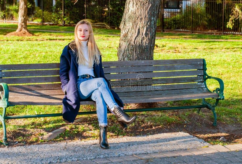 Bella donna che si siede sul banco nel giorno soleggiato di autunno nel parco fotografia stock