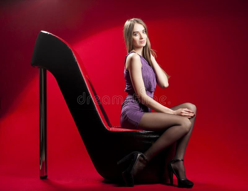 Bella donna che si siede sul sofà rosso dell'alto tallone fotografia stock