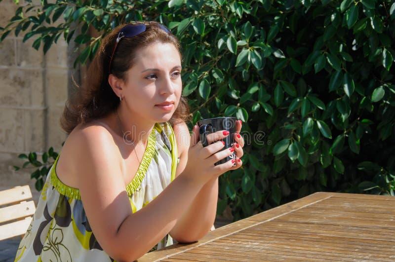 Bella donna che si siede in un caffè bevente del caffè immagine stock