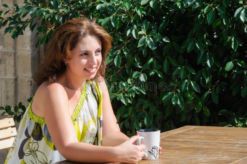 Bella donna che si siede in un caffè bevente del caffè fotografie stock libere da diritti