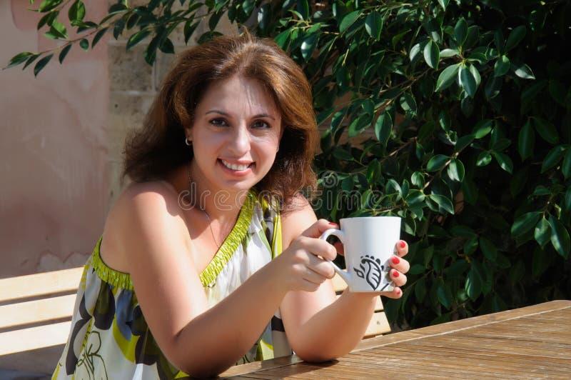 Bella donna che si siede in un caffè bevente del caffè fotografia stock libera da diritti