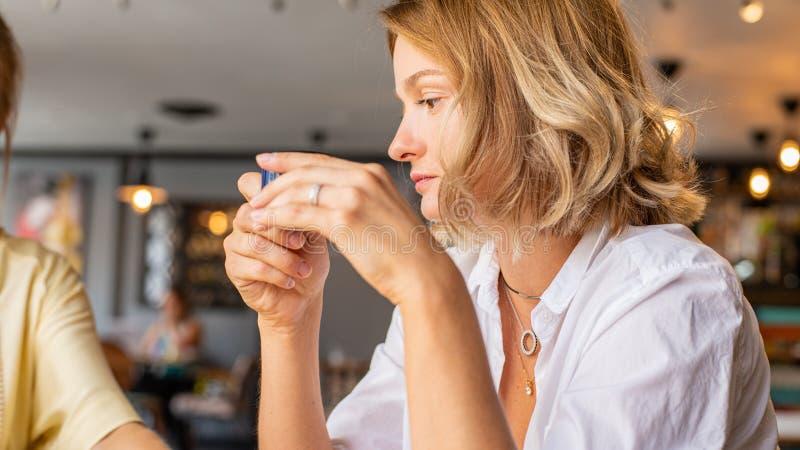 Bella donna che si siede in un caffè con una tazza di caffè La giovane donna attraente sta bevendo il caffè di mattina fotografie stock