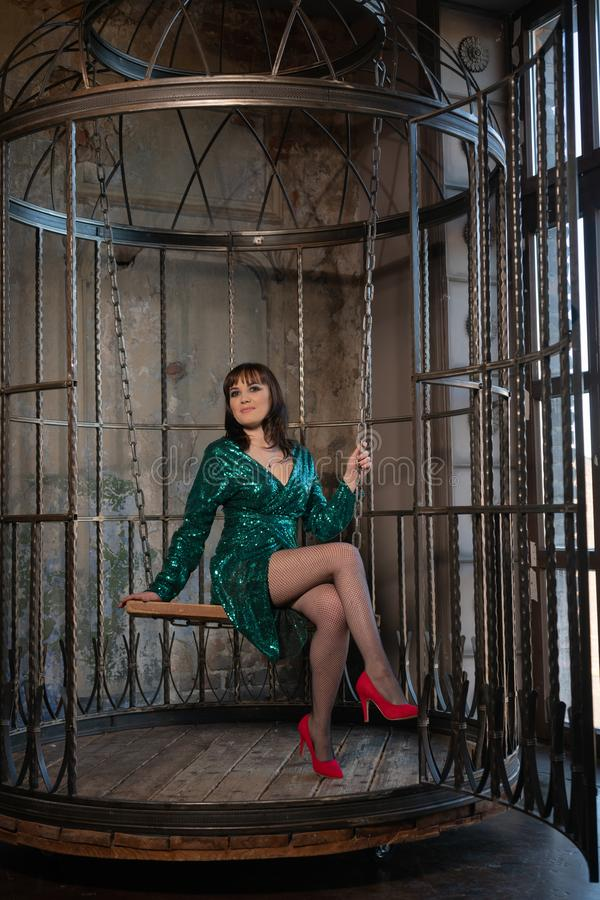 Bella donna che si siede in una gabbia da solo a causa delle suoi limitazioni e complessi vestito uguagliante verde d'uso femmini immagine stock