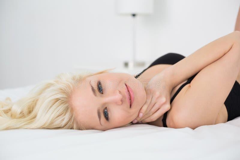 Bella donna che si trova nel reggiseno nero sul letto - Letto che si chiude ...
