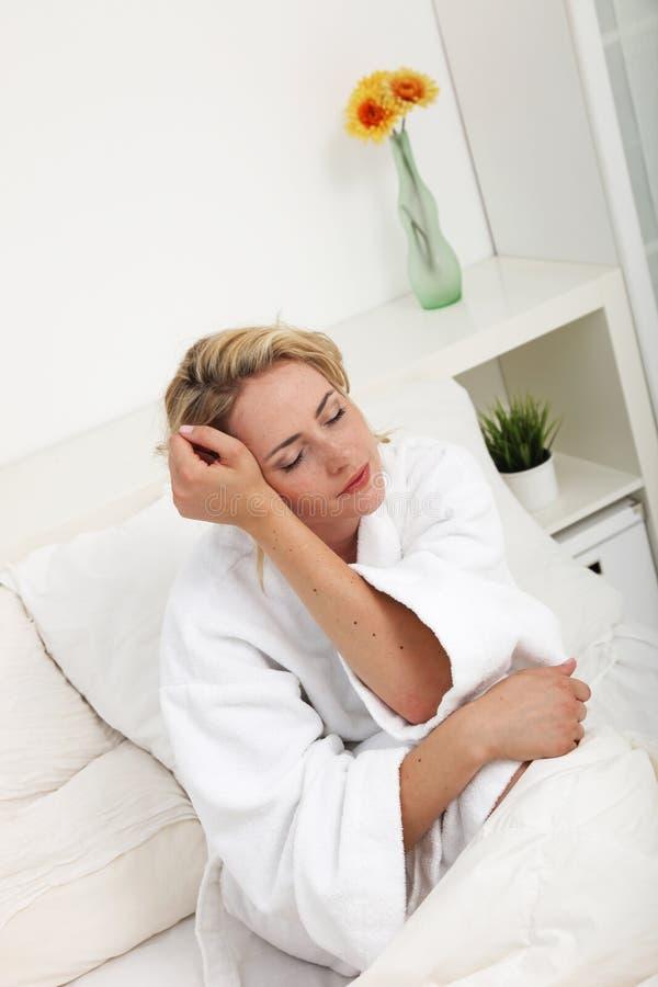 Bella donna che sogna seduta a letto immagini stock