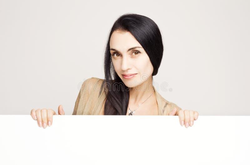 Bella donna che sorride mostrando cartello bianco in bianco immagine stock libera da diritti