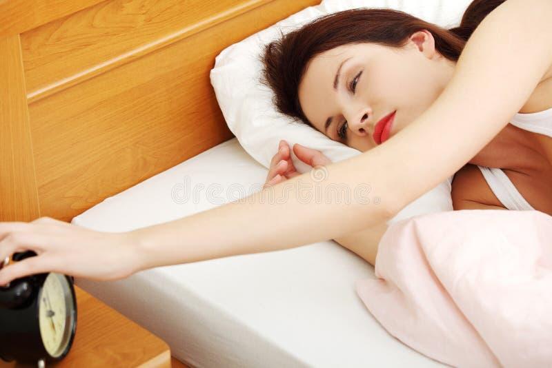Bella donna che spegne una sveglia. fotografie stock